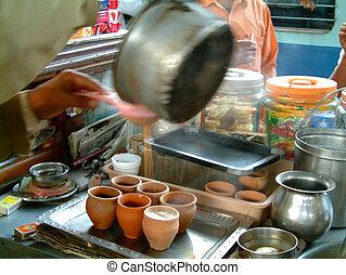 serving chai tea - man serving boiling chai tea in clay...