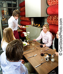 Serving dinner - Waiter serving meals in a restaurant to a...