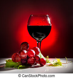 serving glass of red wine and grapevine with green leaf