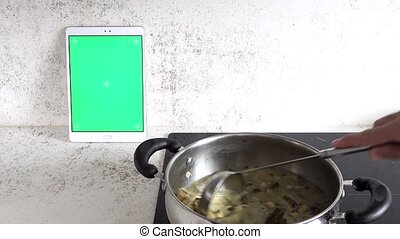 Serving laddle from chockpea stew and tablet with chroma ...