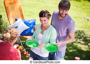 Serving meal on garden party - Woman serving meal on...