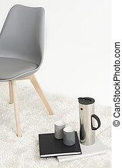 Serving of coffee alongside a modern chair
