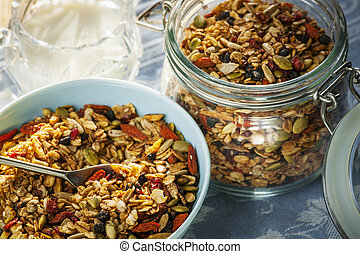 Serving of homemade granola in blue bowl and milk or yogurt...