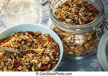 Serving of homemade granola in blue bowl and milk or yogurt...