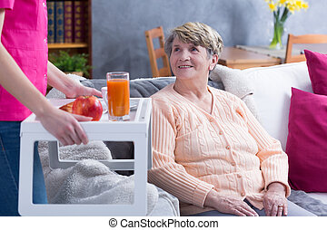 Serving senior woman juice - Home caregiver serving senior...