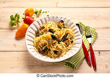 Serving size of pasta with mussels tabletop photography