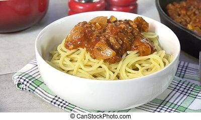 Serving Spaghetti Sauce - Spooning spaghetti sauce onto...