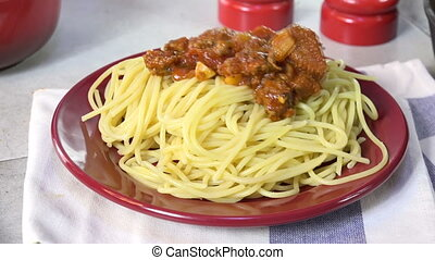 Serving spaghetti - Spooning spaghetti sauce with meat onto...