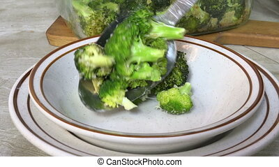 Serving steamed broccoli - Spooning hot steaming broccoli...
