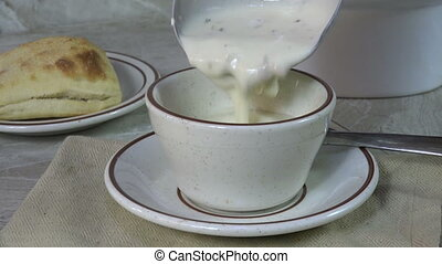 Serving steaming hot clam chowder - Serving clam chowder...