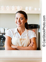 Serving the best coffee in town. Beautiful young woman in apron keeping arms crossed while standing in coffee shop