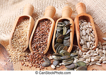 Sesame, flax, pumpkin and sunflower seeds in wooden spoons