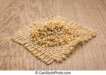 Sesame. Grains on square cutout of jute. Wooden table. Selective focus.