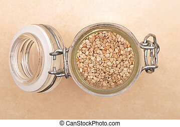 Sesame in small glass on brown background