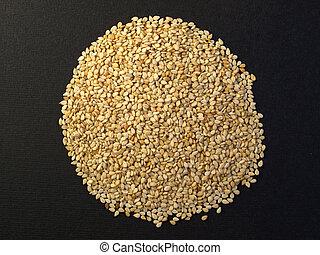 A heap of brown yellow sesame seeds