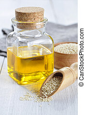 Sesame seeds and oil in a glass bottle on a wooden ...