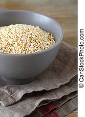 Sesame seeds in a bowl on boards