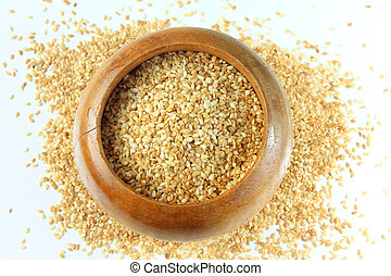 Sesame seeds in wooden spoon isolated on white background, top view.