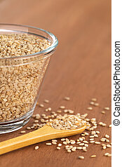 Sesame Seeds - Sesame seeds on small wooden spoon with a...