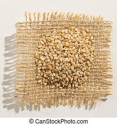 Sesamo. Close up of grains over burlap.