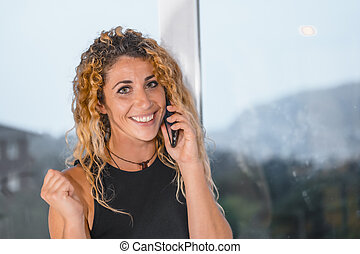 Session young entrepreneurs in the office, 1 young blonde Caucasian woman with curly hair talking on the phone in the office