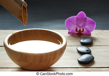 Set for spa procedures, stones for hot massage and flavored water, recruited from a bamboo stem into a bowl