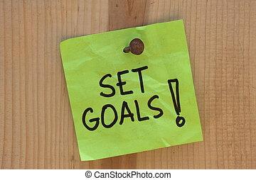 Set goals - motivational reminder on post note nailed to...