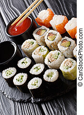 Set Japanese rolls assortment maki, uramaki, hosomaki are served on a stone board. vertical