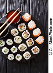 Set Japanese rolls assortment maki, uramaki, hosomaki are served on a stone board. Vertical top view