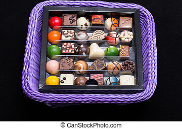 Set of a various chocolate pralines in lavender basket