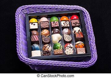 Set of a various chocolate pralines in lavender basket