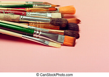 Set of art paint brushes over pastel pink background. Painting supplies, art concept