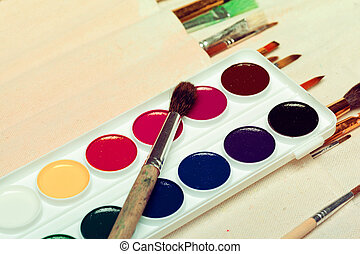 Set of art paint brushes with watercolors close up