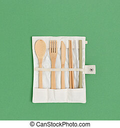 Set of bamboo cutlery in a case on a green pastel background.