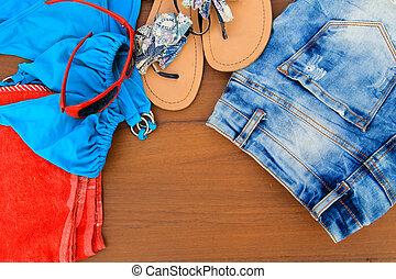 Set of beachwear on wooden background