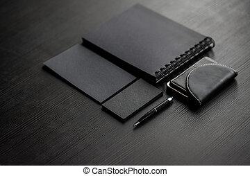 Set of black mockups on dark background, female hand holding...