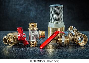 set of brass pipe connectors ondark background