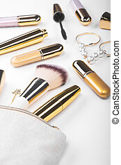 Set of brushes and cosmetic products in a cosmetic bag on a white background