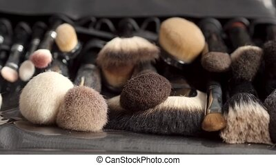 Set of brushes for makeup scattered on wooden background