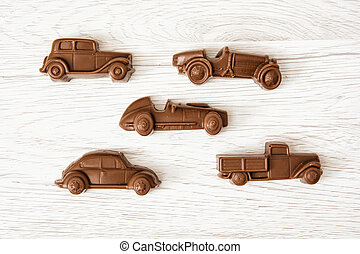 Set of chocolate car figures on wooden background