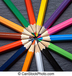 Set of color pencils in shape of sun on grey wooden background.