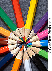 Set of color sharpened pencils close up in shape of sun on grey wooden background.