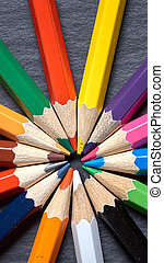 Set of color sharpened pencils in shape of sun on grey wooden background.