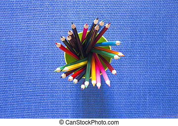 Set of colored pencils in a glass on a blue background, top view