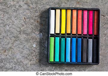 Set of colorful chalk stick on black tray
