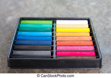 Set of colorful chalk stick on black tray