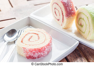 Set of colorful jam rolls with spoon and fork