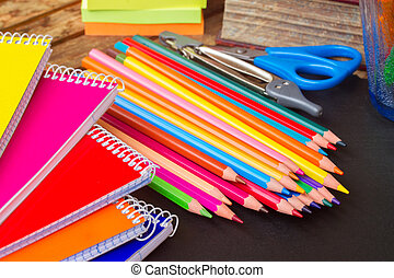 Set of colorful pencils on black board