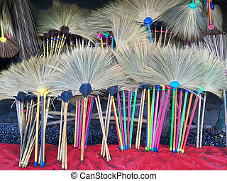 colorful straw brooms at grocery store