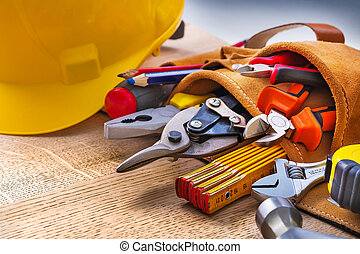 set of construction tools in toolbelt close up on wooden board